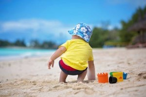120399711-cute-toddler-baby-boy-playing-with-siblings-with-beach-toys-on-tropical-beach